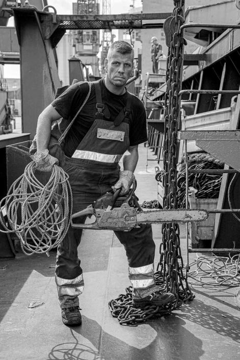 Hafenarbeiter Lascher Portrait mit Kettensäge © Hermann Jansen