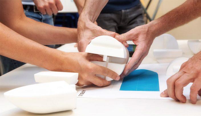 Interaktives Spiel zum Thema Teambuilding Team Hände haltenTeile von Flugzeugmodell © Hermann Jansen