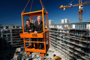 Vorstand der Baugenossenschaft DHU im Krankorb über Baustelle schwebend PR-Bild Award Platz 2 © Hermann Jansen